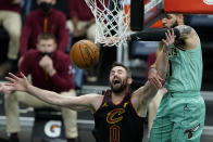 Charlotte Hornets forward Cody Martin, right, passes around Cleveland Cavaliers forward Kevin Love during the second half of an NBA basketball game on Friday, April 23, 2021, in Charlotte, N.C. (AP Photo/Chris Carlson)