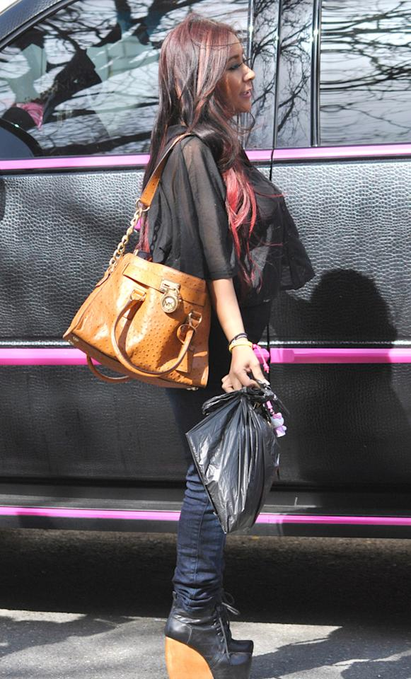 Snooki is seen in front of her Escalade wearing laced-up wedge boots on March 26, 2012.