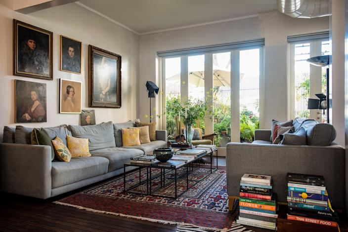 In the living space, the iron tables were crafted by a local artist and the wall above the sofa showcases a collection of paintings by 19th-century art students.