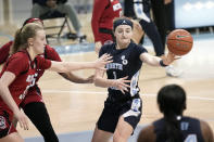 North Carolina guard Alyssa Ustby (1) passes while North Carolina State center Elissa Cunane (33) reaches in during the second half of an NCAA college basketball game in Chapel Hill, N.C., Sunday, Feb. 7, 2021. (AP Photo/Gerry Broome)