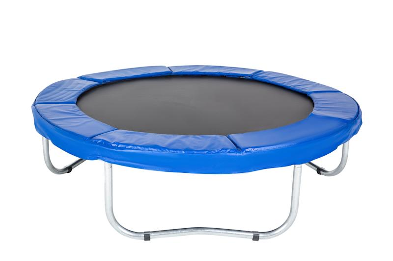 Trampoline for children and adults for fun indoor or outdoor fitness jumping on white background. Blue trampoline Isolated.