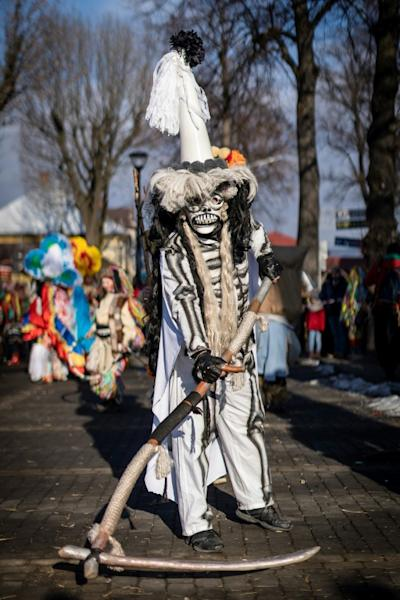 "Amid the din, the Grim Reaper cuts a calm figure as he waves his scythe at onlookers, although popular tradition has it that death merely marks the passage to ""a new and higher stage of life,"" says ethnographer Barbara Rosiek (AFP Photo/Wojtek RADWANSKI)"