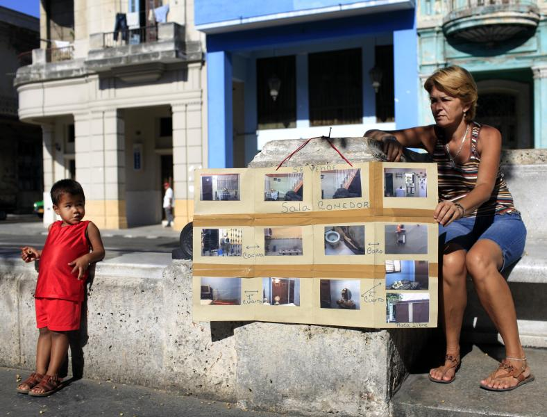 In this April 19, 2013 photo, Estrella Diaz sits next to a homemade sign advertising her home for sale, in Havana, Cuba. A baffling, sometimes bizarre real estate market has emerged in the year and a half since President Raul Castro legalized private home sales for the first time in five decades. The market still lacks a workable mortgage system, an easy means of advertising potential sales and, most important, a middle class with resources to buy. (AP Photo/Franklin Reyes)