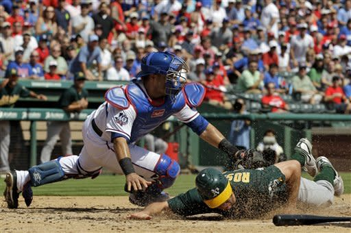 Oakland Athletics' Adam Rosales scores at under the attempted tag by Texas Rangers' Geovany Soto during the third inning of a baseball game Thursday, Sept. 27, 2012, in Arlington, Texas. Rosales reached home safely on a Jonny Gomes double. (AP Photo/Tony Gutierrez)
