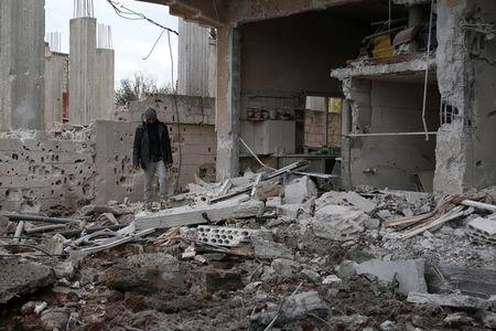 A man inspects a damaged house after an airstrike on al-Yadouda village, in Deraa Governorate