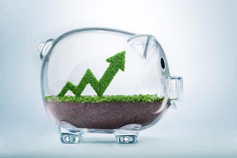 A glass jar in the shape of a piggy bank with an upward trending arrow made out of grass inside the jar.