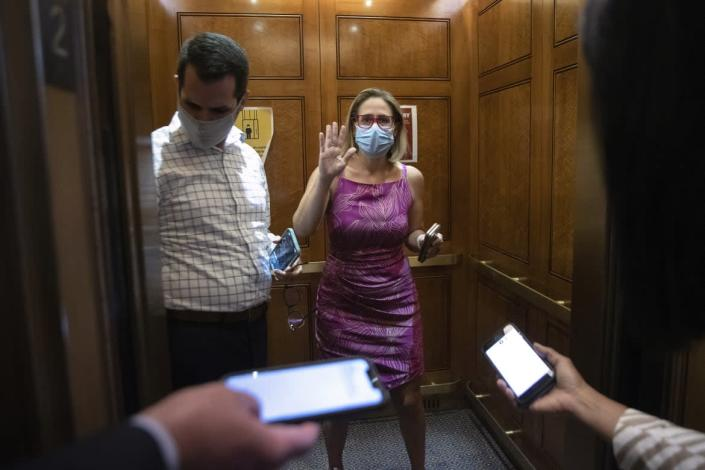 """<div class=""""inline-image__caption""""><p>Sen. Sinema speaks briefly to reporters as she boards an elevator following votes on Sept. 20, 2021 in Washington, DC. </p></div> <div class=""""inline-image__credit"""">Chip Somodevilla/Getty Images</div>"""