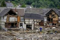 FOR HOLD -FILE - In this Thursday, July 15, 2021, file photo, a person stands in front of destroyed houses in Schuld, Germany, after massive floods in the region. Germany's parliament last week approved a 30 billion-Euro, 35 billion Dollars, rebuilding fund for the swath of western Germany affected by the flooding. Overseeing that long-term effort will fall to Germany's next administration. (AP Photo/Michael Probst, File)