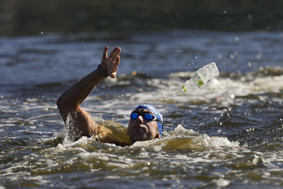 Athanasios Kynigakis, of Greece, tosses his battle at a feeding station during the men's marathon swimming event at the 2020 Summer Olympics, Thursday, Aug. 5, 2021, in Tokyo, Japan. (AP Photo/Jae C. Hong)