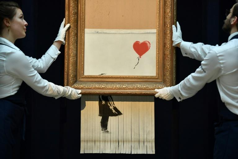 "Moments after Banksy's ""Girl with Balloon"" sold at Sotheby's it unexpectedly passed through a shredder hidden in the frame"