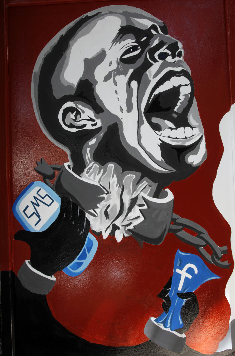 """FILE - In this March 30, 2011, file photo, a mural depicting a man in shackles and the Facebook logo and a mobile phone is seen on the wall of the University of Helwan arts academy in the Zamalek neighborhood of Cairo, Egypt. The team from the CIA's Open Source Center, housed in a unassuming brick building in a Virginia industrial park, pores daily over tweets, Facebook, newspapers, TV news channels, local radio stations, Internet chat rooms _ anything overseas that anyone can access, and contribute to, openly. The center saw the uprising in Egypt coming said the center's director, Doug Naquin. The center already had """"predicted that social media in places like Egypt could be a game-changer and a threat to the regime,"""" he said in a recent interview with The Associated Press.  (AP Photo/Manoocher Deghati, File)"""