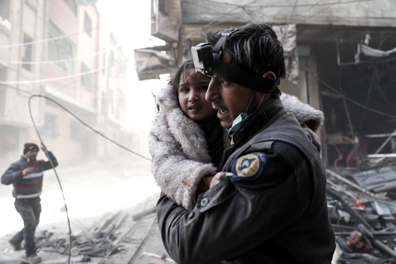 A Syrian White Helmets rescue worker carries a girl from the site of a government airstrike on the rebel-held town of Douma, on the eastern outskirts of Damascus, on February 25, 2017