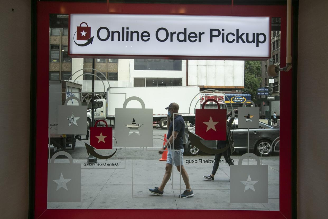Pedestrians pass the online order pickup area at the Macy's Herald Square location on Friday, June 19, 2020, in New York.