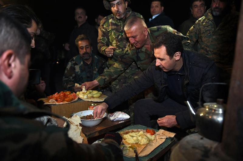 Handout picture by the Syrian Arab News Agency shows Syrian President Bashar al-Assad (R) sharing a meal with troops during a reported visit to eastern Damascus district Jobar as government forces and rebels continue their fight for control (AFP Photo/)