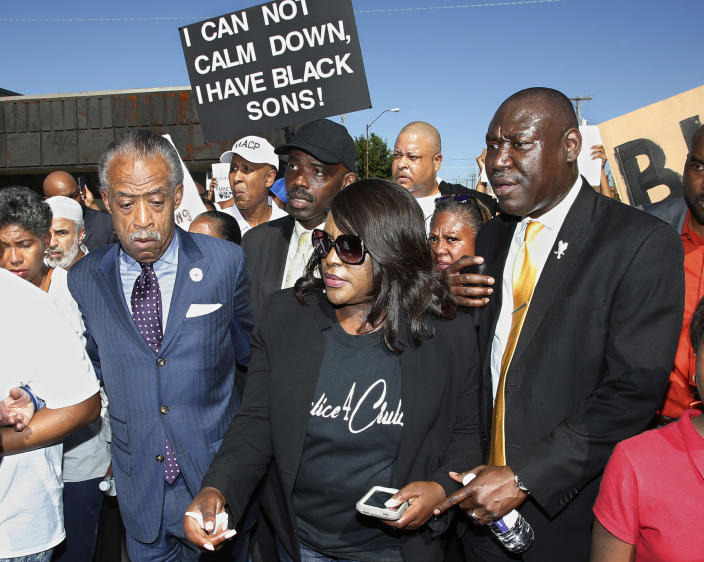 Tiffany Crutcher, center, the twin sister of Terence Crutcher, who was killed by a Tulsa police officer, marches with the Rev. Al Sharpton, left, and attorney Benjamin Crump, right, in Tulsa, Okla., on Sept. 27, 2016. (Sue Ogrocki / AP file)