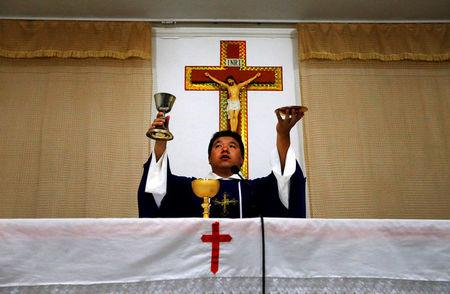 FILE PHOTO: Catholic priest Liu performs holy communion in a make-shift chapel in the village of Bai Gu Tun, located on the outskirts of the city of Tianjin, around 70 km south-east of Beijing