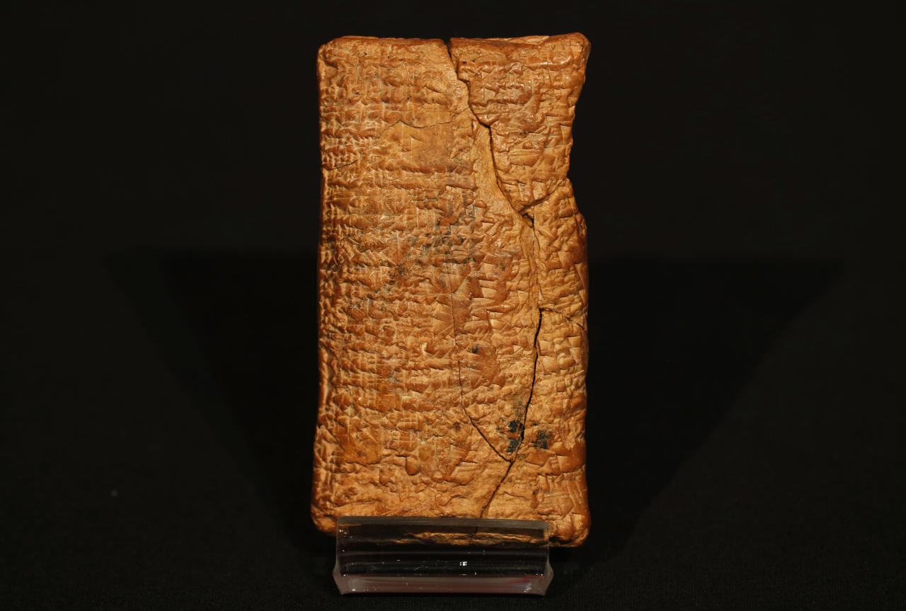 The 4000 year old clay tablet containing the story of the Ark and the flood stands on display at the British Museum in London during the launch of the book 'The Ark Before Noah' by Irving Finkel, curator in charge of cuneiform clay tablets at the British Museum, Friday, Jan. 24, 2014. The book tells how he decoded the story of the Flood and offers a new understanding of the Old Testament's central narratives and how the flood story entered into it. (AP Photo/Sang Tan)