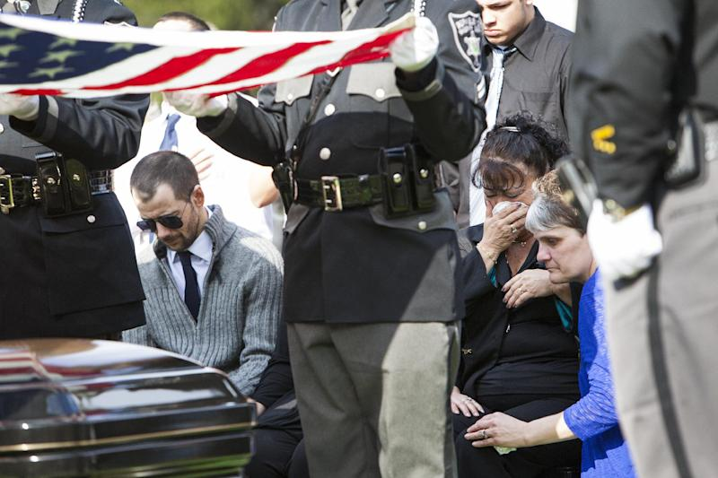 "Eugene ""Bub"" Crum, left, bows his head as Lynette Morrison, right, comforts his mother Rosie Crum on Sunday, April 7, 2013, at Lenore Memorial Gardens in Lenore, W.Va. Law enforcement officials, family, friends and community leaders gathered for the burial service for the late Mingo County Sheriff Eugene Crum who was gunned down just after three months in office. Rosie Crum, his wife, was sworn in as the new sheriff. (AP Photo/Randy Snyder)"