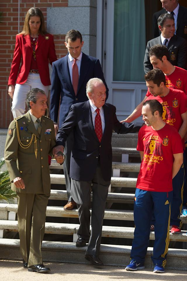 MADRID, SPAIN - JULY 02: King Juan Carlos I of Spain (C) is helped down some steps in front of Prince Felipe of Spain and Princess Elena of Spain as he speaks with Andres Iniesta (front), Jordi Alba (C) and Juanfran of Spain as he receives members of Spain's victorious UEFA EURO 2012 football squad at Zarzuela Palace on July 2, 2012 in Madrid, Spain. (Photo by Pool/Getty Images)