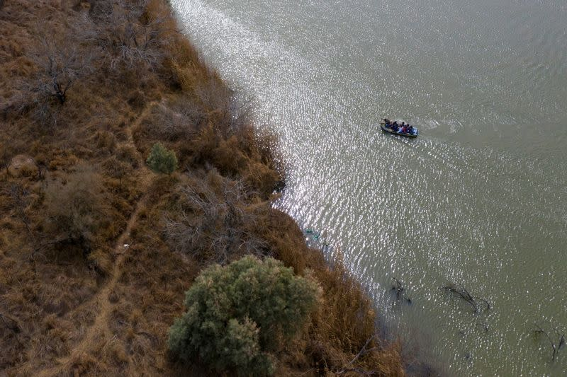 Smugglers use raft to transport migrant families and children into the United States from Mexico in Penitas, Texas
