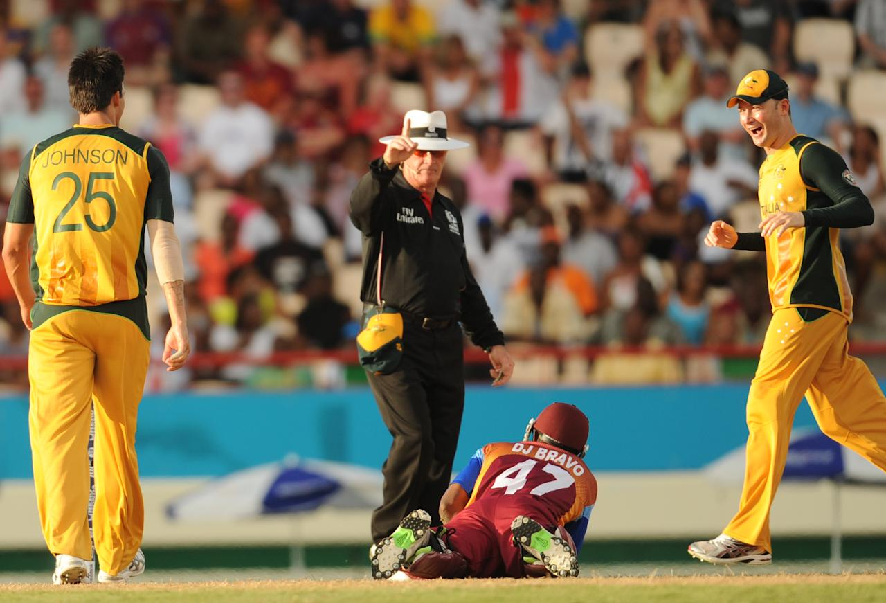 Australian cricketers Mitchell Johnson (L) and Michael Clarkereact as Umpire Rudi Koertzen of South Africa signals the run-out of West Indies cricketer Dwayne Bravo during the ICC World Twenty20 Super Eight match between West Indies and Australia at the Beausejour Cricket Ground on May 11, 2010 in Gros Islet, St Lucia. AFP PHOTO/Indranil MUKHERJEE (Photo credit should read INDRANIL MUKHERJEE/AFP/Getty Images)