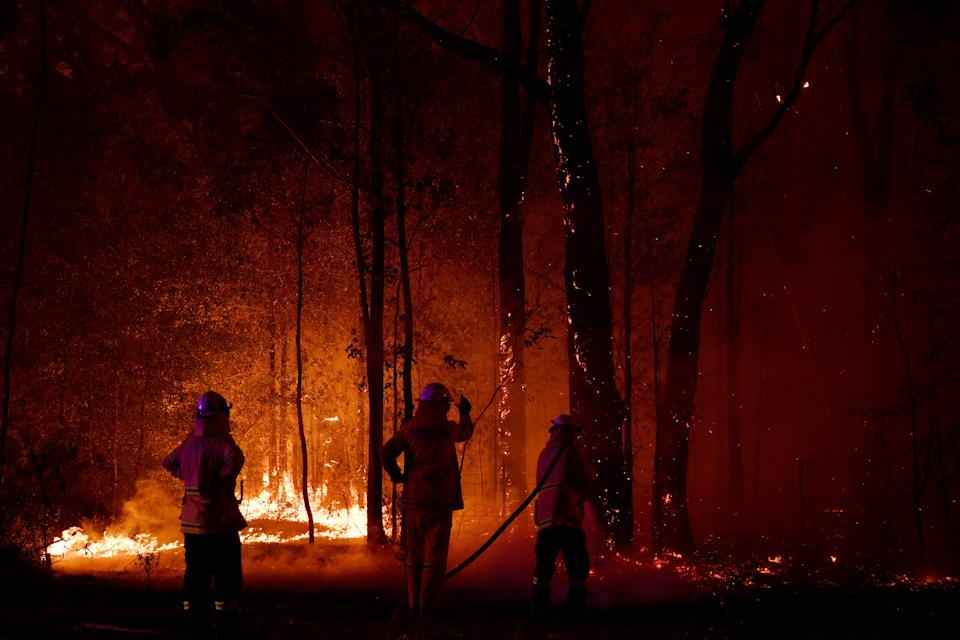 A Rural Fire Service (RFS) firefighter conducts mopping up near the town of Sussex Inlet on December 31. Source: Getty