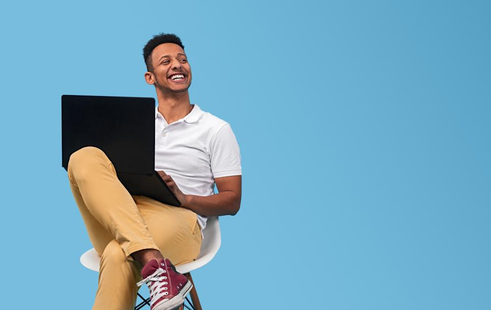 Young man smiling and looking at empty space while sitting on chair and using laptop against blue background
