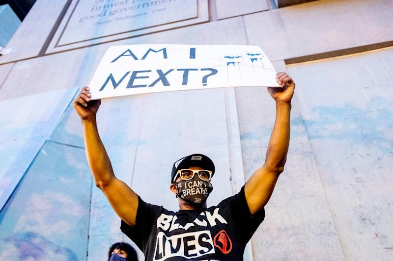 Romeo Ceasar holds a sign during a Black Lives Matter protester on Monday, July 20, 2020, in Portland, Oregon.
