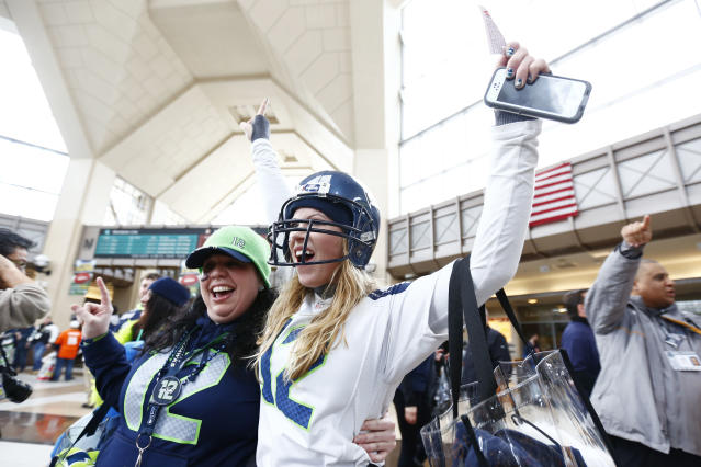 Football fans cheer at the Secaucus Junction, Sunday, Feb. 2, 2014, in Secaucus, N.J. The Seattle Seahawks are scheduled to play the Denver Broncos in the NFL Super Bowl XLVIII football game on Sunday evening at MetLife Stadium in East Rutherford, N.J. (AP Photo/Matt Rourke)