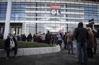 People wait outside as they arrive to be vaccinated against Covid-19 the opening day of a mass vaccination centre set up in the Olympique Lyonnais soccer Stadium, in Decines-Charpieu, Saturday, April 3, 2021. (Jean-Philippe Ksiazek, Pool via AP)