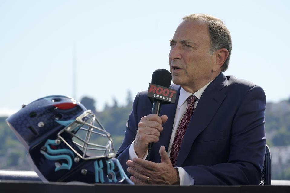 NHL Commissioner Gary Bettman takes part in an interview next to a Seattle Kraken NHL hockey goalie helmet Wednesday, July 21, 2021, during the Kraken's expansion draft event in Seattle. (AP Photo/Ted S. Warren)