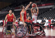 Nikola Concin of Canada shoots marked by Manuel Lorenzo Diaz, center, of Spain during the men's wheelchair basketball Group A game at the Tokyo 2020 Paralympic Games in Tokyo Thursday, Aug. 26, 2021. (Bob Martin for OIS via AP)