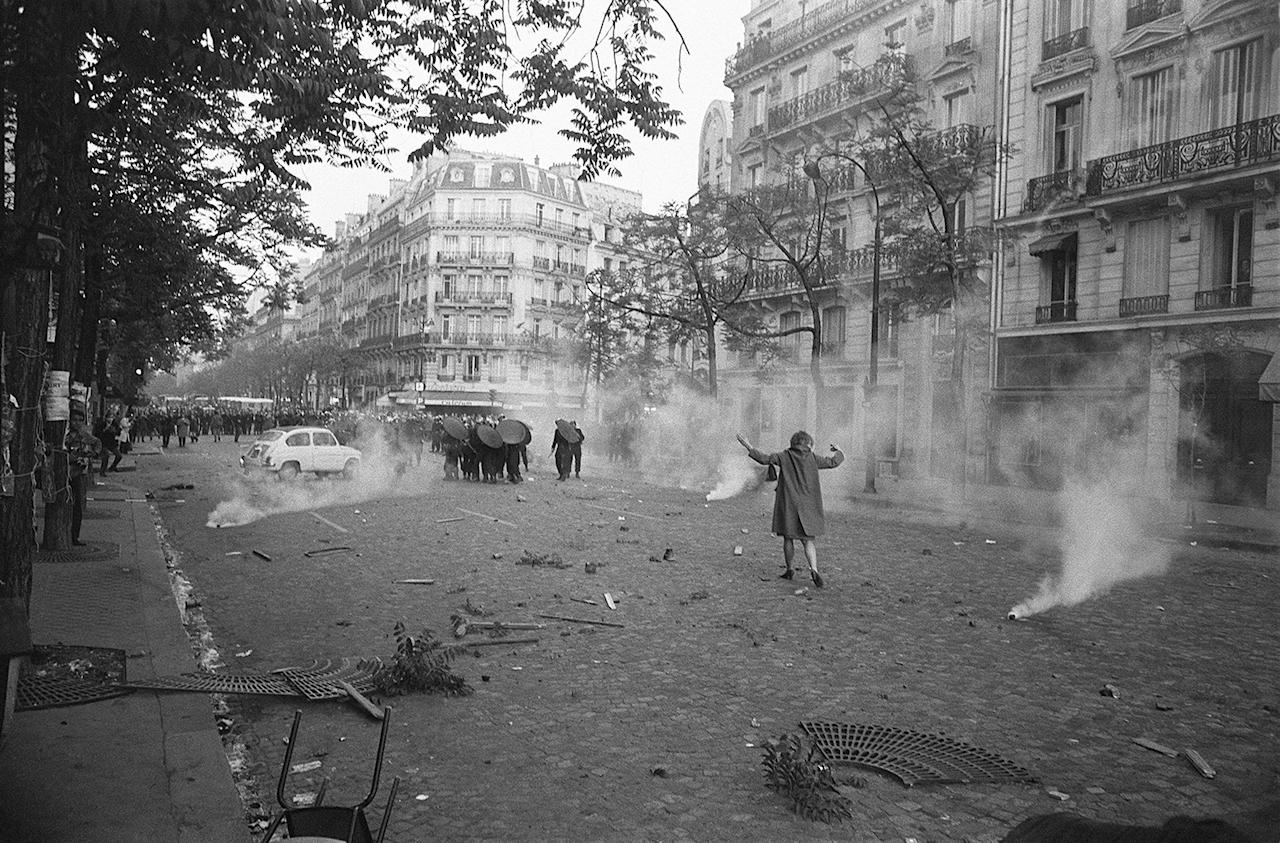 <p>On the first day of violence during student riots, a young woman challenges shield-bearing CRS police in a cloud of tear gas at Place Mabillon on the Boulevard Saint-Germain in Paris, May 6, 1968. (Photo: Gökşin Sipahioğlu/SIPA) </p>