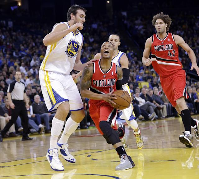 Portland Trail Blazers' Damian Lillard (0) drives to the basket as Golden State Warriors' Andrew Bogut (12) defends during the first half of an NBA basketball game on Sunday, Jan. 26, 2014, in Oakland, Calif. (AP Photo/Marcio Jose Sanchez)