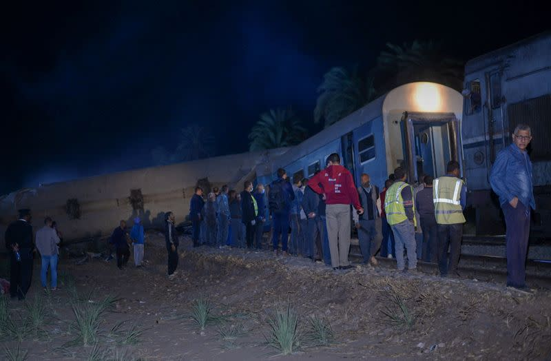 People view the damage after two trains have collided near the city of Sohag