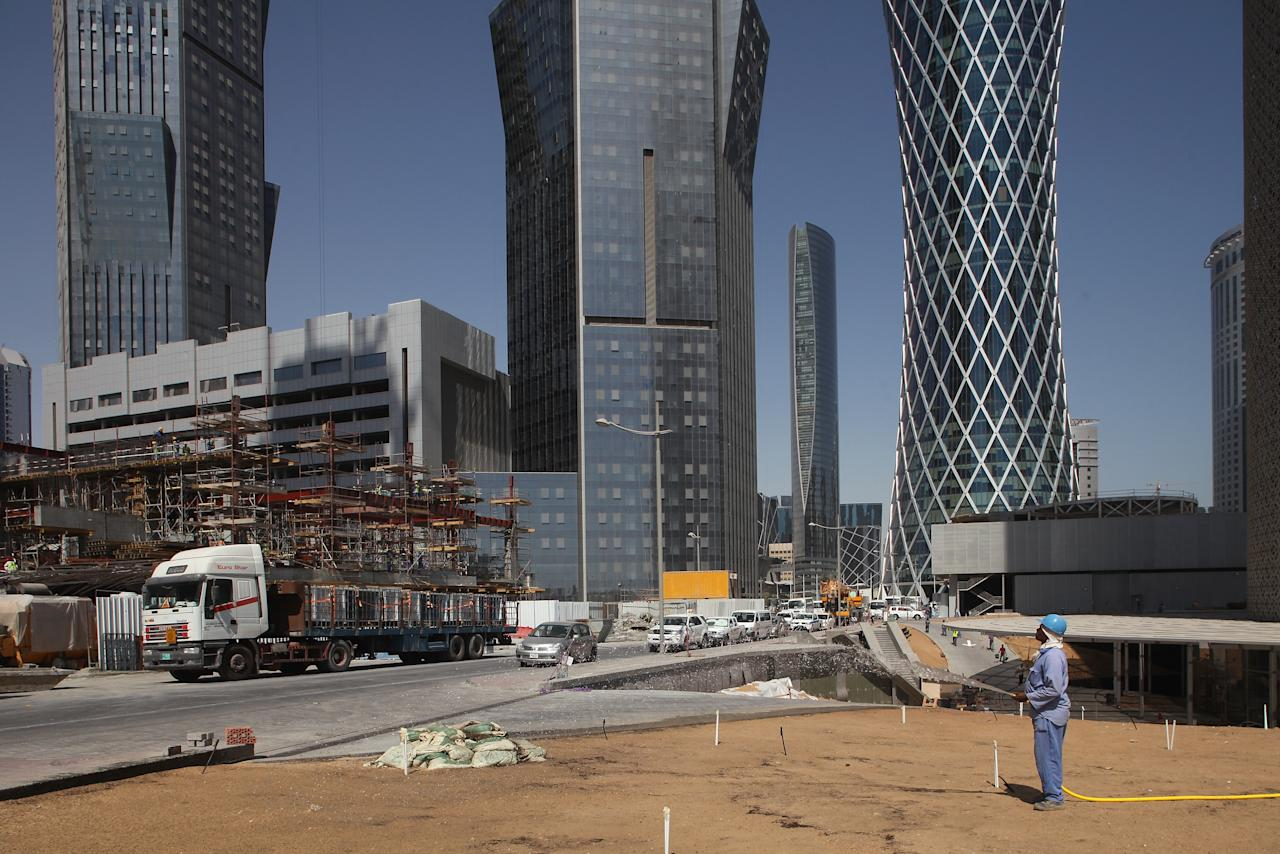 DOHA, QATAR - OCTOBER 23:  (EDITORS NOTE: Image was created using a variable planed lens.)  A workers waters baren ground next to new office buildings, including the Tornado Tower (R), by SIAT Architekten of Munich in the budding new financial district on October 23, 2011 in Doha, Qatar. Qatar will host the 2022 FIFA World Cup football competition and is slated to tackle a variety of infrastructure projects, including the construction of new stadiums.  (Photo by Sean Gallup/Getty Images)
