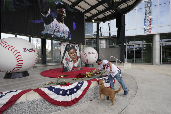 A man places flowers next to a portrait Atlanta Braves' Hank Aaron outside Truist Park, Friday, Jan. 22, 2021, in Atlanta. Aaron, who endured racist threats with stoic dignity during his pursuit of Babe Ruth but went on to break the career home run record in the pre-steroids era, died peacefully in his sleep early Friday. He was 86. (AP Photo/John Bazemore