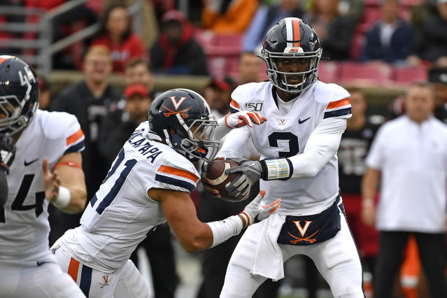 Virginia quarterback Bryce Perkins (3) makes a handoff to running back Wayne Taulapapa (21) during the first half of an NCAA college football game in Louisville, Ky., Saturday, Oct. 26, 2019. (AP Photo/Timothy D. Easley)