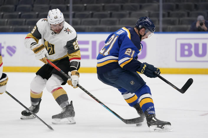 Vegas Golden Knights' William Carrier (28) reaches for the puck as St. Louis Blues' Tyler Bozak (21) skates past during the second period of an NHL hockey game Wednesday, April 7, 2021, in St. Louis. (AP Photo/Jeff Roberson)