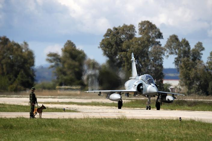 A Greek crew of a Mirage 2000-5 taxis as a soldier with a dog guards at Andravida air base, about 279 kilometres (174 miles) southwest of Athens, Tuesday, April 20, 2021. Greece vowed Tuesday to expand military cooperation with traditional NATO allies as well as Middle Eastern powers in a race to modernize its armed forces and face its militarily assertive neighbor Turkey. (AP Photo/Thanassis Stavrakis)
