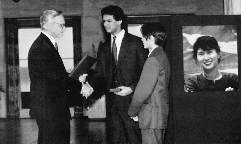 """FILE - In this Tuesday, Dec. 10, 1991 file photo, Alexander Aris, center, the teenage son of imprisoned Nobel Peace Prize laureate Aung San Suu Kyi, shown in poster at right, accepts the Nobel Peace Prize """"in the name of all the people of Burma,"""" from the head of the Norwegian Nobel Peace Prize Committe, Francis Sejersted, left, during the award ceremony in Oslo, Norway. At right is Suu Kyi's son, Kim. (AP Photo/Bjoern Sigurdsoen)"""