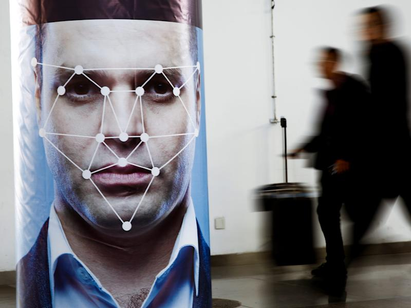 People walk past a poster simulating facial recognition software at the Security China 2018 exhibition
