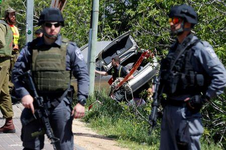 Israeli policemen stand guard at the scene of a Palestinian car ramming attack near the Jewish settlement of Ofra near the West Bank city of Ramallah
