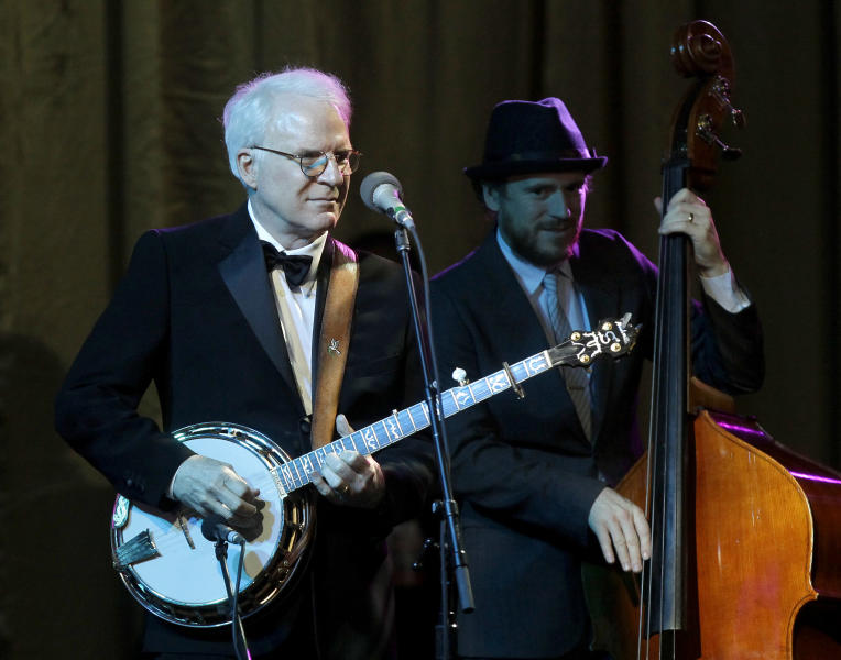 FILE - In this Saturday, March 23, 2013, file photo, honored guest Steve Martin, left, performs with his band The Steep Canyon Rangers at Muhammad Ali's Celebrity Fight Night XIX at the JW Marriott Desert Ridge Resort and Spa, in Phoenix. Martin and his bluegrass band are returning as one of the headliners for the Xerox Rochester International Jazz Festival in June. (Photo by Rick Scuteri/Invision/AP, File)