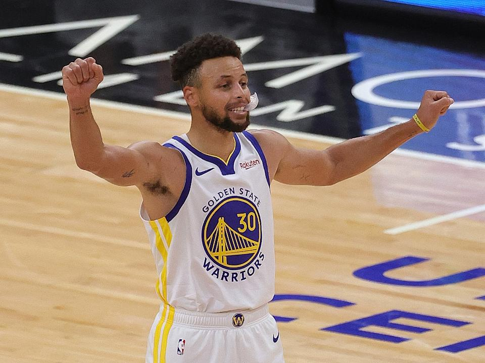 Stephen Curry raises his arms to react during a game.