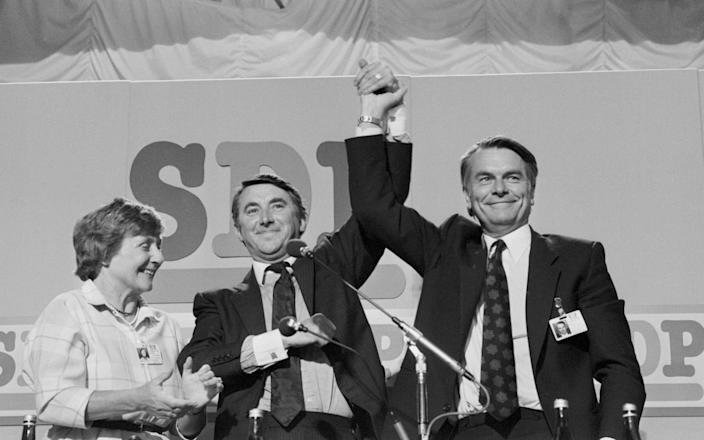 Social Democratic Party President Shirley Williams applauding Liberal leader David Steel, centre, who has joined hands with SDP leader Dr David Owen after Mr Steel's speech to the SDP conference in Torquay, 1985 - PA
