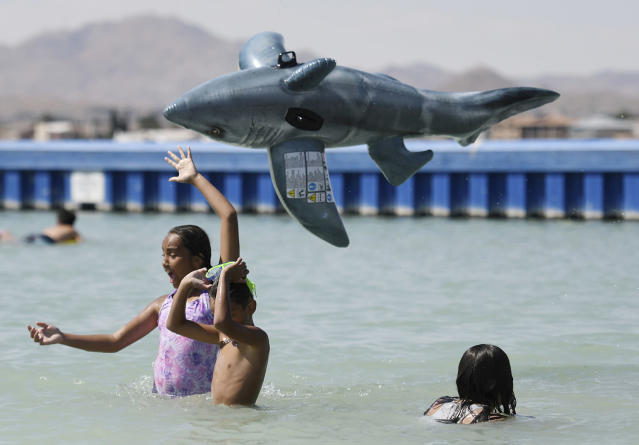 <p>Carolina Colon tosses a shark water toy airborne while cooling off at Spring Valley Lake in Victorville Calif., June 19, 2017. (James Quigg/The Daily Press via AP) </p>