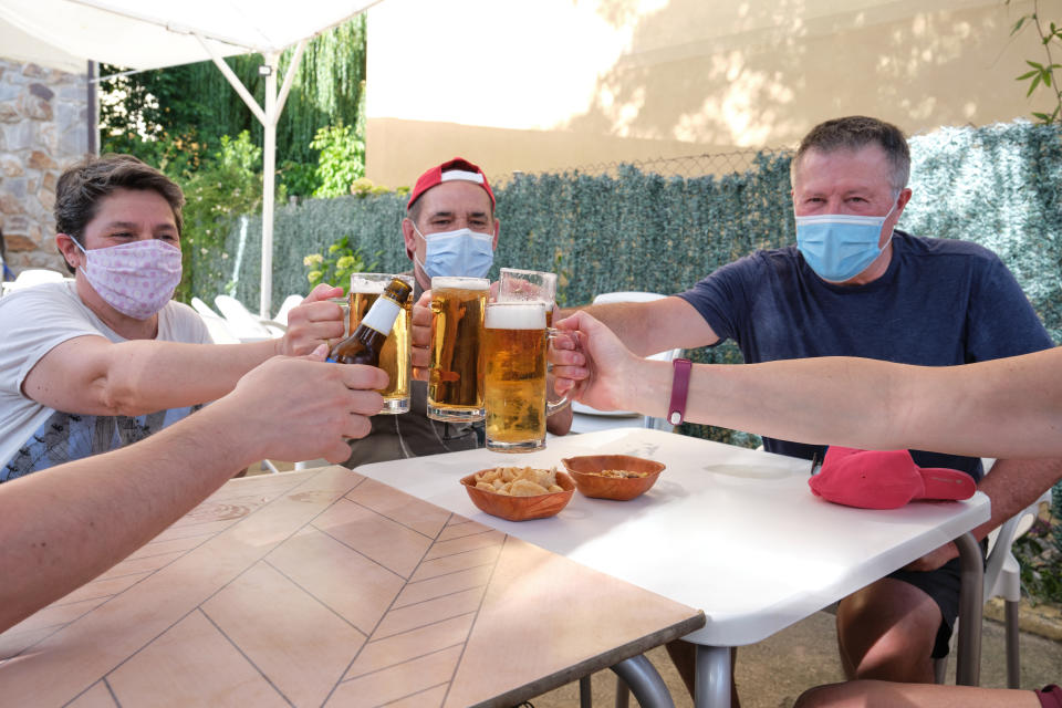 People with face masks cheering with beers in a bar. New normality in bars concept.