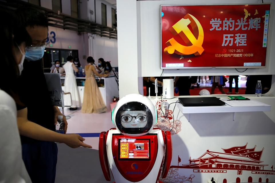 A staff member introduces a robot developed by Chuangze and installed with a system designed for political education of Communist Party of China, at the Beijing World Robot Conference 2021 in Beijing, China September 10, 2021. REUTERS/Tingshu Wang