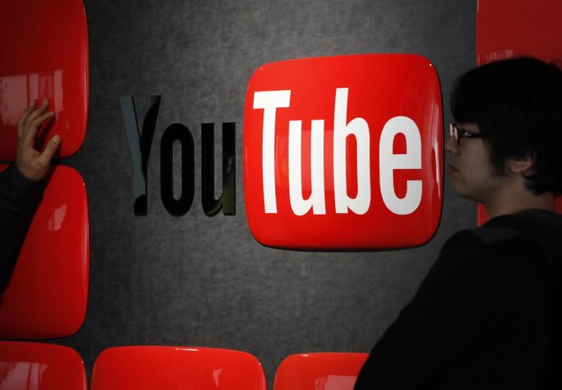 Visitors stand in front of a logo of YouTube at the YouTube Space Tokyo, operated by Google, in Tokyo